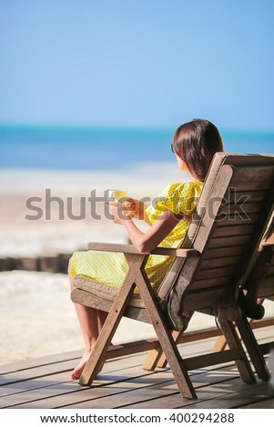 Happy woman drinking coffee cappuccino enjoying beach view