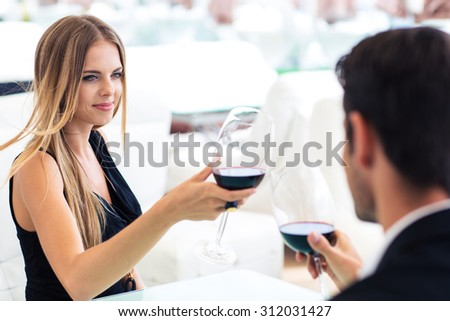 Happy woman drinking red wine with boyfriend in restaurant