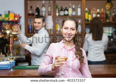 Happy woman drinking wine at counter and chatting with bartenders
