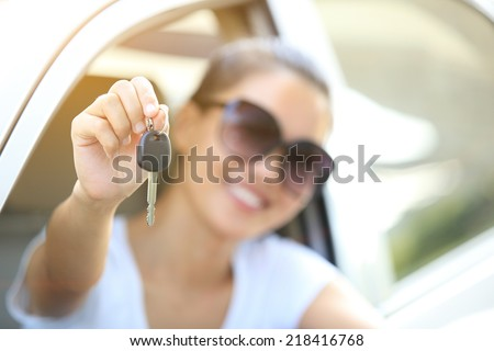 happy woman driver hold car keys in her new car