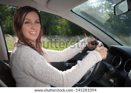 Happy woman driving a car and holding the steering wheel