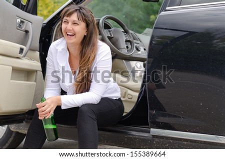 Happy woman drunkard in a car sitting on the sill of the open drivers door clasping her bottle of spirits and laughing - stock photo