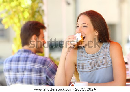 Happy woman eating a cupcake in a coffee shop terrace - stock photo