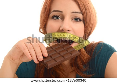 Happy woman eating a yummy chocolate and having some sugar for an active day during diet, with a centimeter on her mouth - stock photo