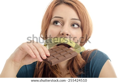 Happy woman eating a yummy chocolate and having some sugar for an active day during diet, with a centimeter on her mouth. Dieting without sweets - stock photo