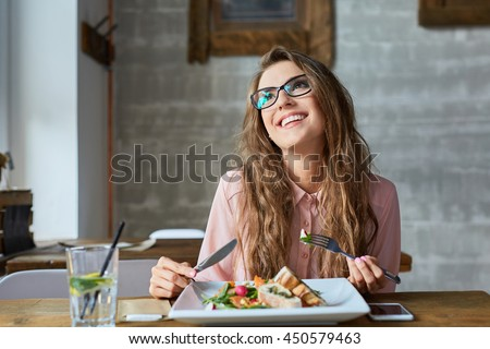 Happy woman eating lunch in restaurant
