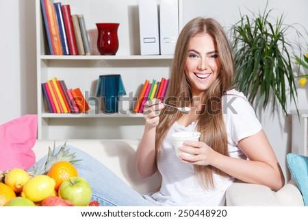 Happy woman eating yogurt - stock photo