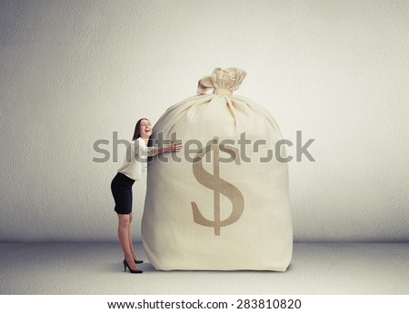 happy woman embracing big bag with money and smiling in empty grey room