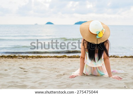 Happy woman enjoying beach relaxing joyful in summer by tropical blue water