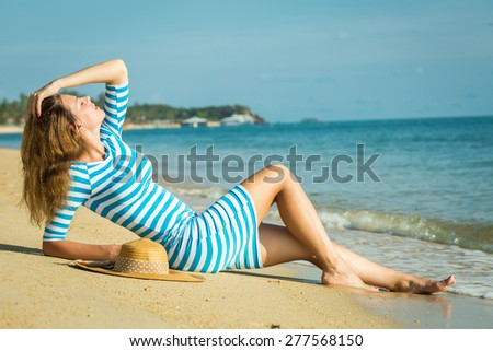 Happy woman enjoying beach relaxing joyful in summer by tropical blue water. Beautiful model happy on travel wearing beach sun hat on Samui beach, Thailand