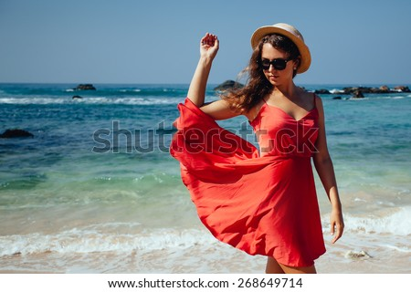 Happy woman enjoying beach relaxing joyful in summer by tropical blue water. Beautiful red dress model happy on travel wearing beach sun straw hat on sandy beach