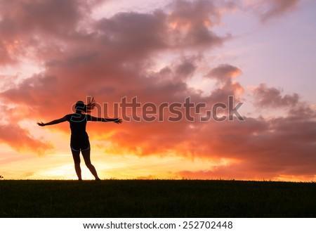 Happy woman enjoying beautiful sunset. Freedom, happiness and enjoyment concept. - stock photo