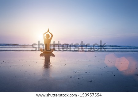 Happy woman enjoying healthy yoga practice at sunrise on a beautiful sandy beach in Koh Chang, Thailand - stock photo
