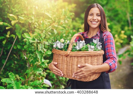 Happy woman enjoying her work at the nursery standing outdoors in a garden clutching a wicker basket full of fresh white flowers for sale in the florist shop