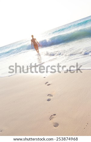 Happy woman enjoying in summer, running joyfully on tropical beach in sunset. Beautiful caucasian model wearing bikini on vacations on sandy beach. Footprints in sand.  - stock photo