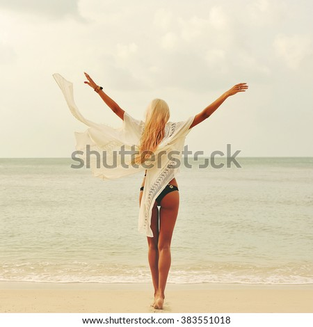 Happy woman enjoying nature at the beach. Arms wide open, freedom  - stock photo