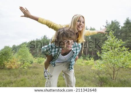 Happy woman enjoying piggyback ride on man in forest - stock photo