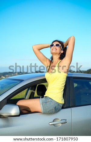 Happy woman enjoying summer vacation on car travel. Blissful female driver portrait. - stock photo