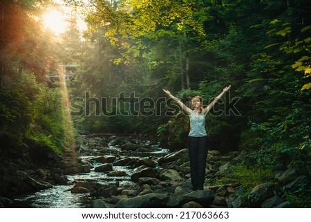 Happy woman enjoying the nature in forest with sunset on background