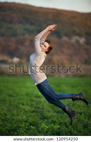 Happy woman Enjoying the nature. Young beautiful girl jumping on fresh air in green field. Provence smiling lady having fun outdoors at sunset - stock photo