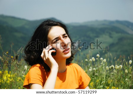 Happy woman enjoying the outdoors talking on her cell phone - stock photo