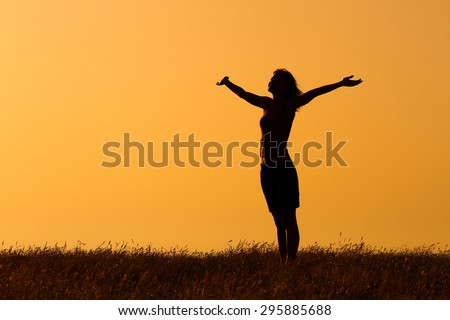 Happy woman enjoys in sunset. Greeting the sunset - stock photo