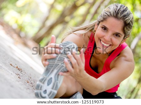 Happy woman exercising at the park and stretching