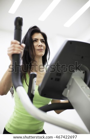 Happy woman exercising with elliptical machine in fitness center