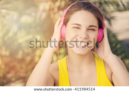 Happy woman exercising with headphones outdoors - stock photo