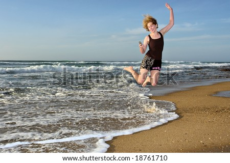Happy woman flies with with mobile phone on beach (sunrise light). Shot in Sodwana Bay Nature Reserve, KwaZulu-Natal province, Southern Mozambique area, South Africa. - stock photo