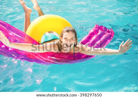 Happy woman floating on air bed in swimming pool - stock photo