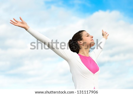 Happy woman freedom blissful concept. Woman with arms up raised to sky relaxing on spring / summer holidays outdoors. Caucasian brunette girl model.