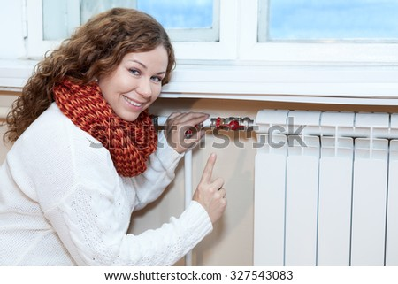 Happy woman gesturing when controlling thermostat on central heating radiator