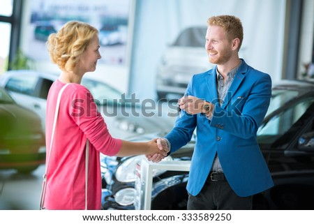 Happy woman  getting car keys from a car seller - stock photo