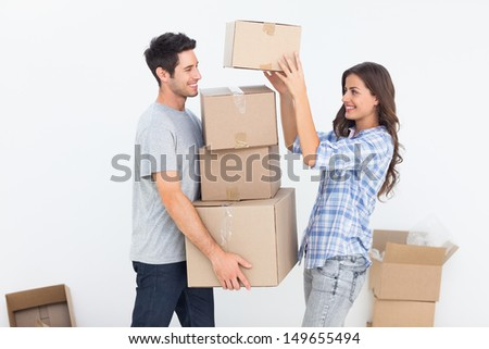 Happy woman giving boxes to her husband while they are moving - stock photo