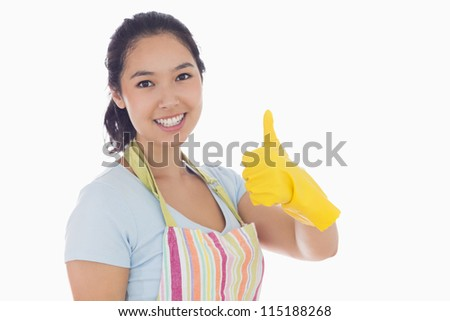 Happy woman giving thumbs up in yellow rubber gloves and apron - stock photo