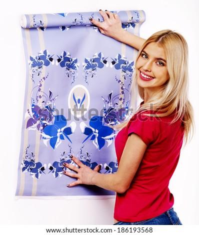 Happy woman glues wallpaper at home. - stock photo