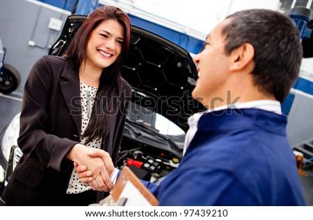 Happy woman handshaking with a mechanic after a good service - stock photo