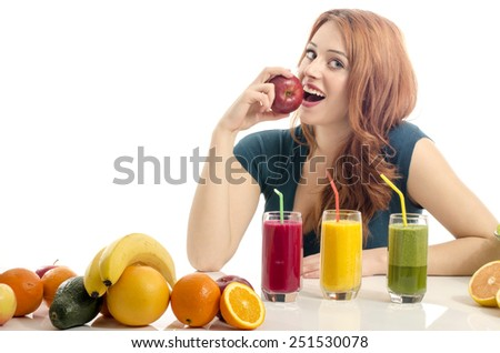 Happy woman having a table full of organic food,juices and smoothie. Cheerful young woman eating healthy salad and fruits. Isolated on white. Girl eating a fresh red apple. - stock photo