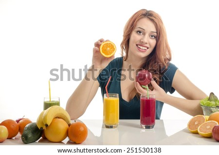 Happy woman having a table full of organic food,juices and smoothie. Cheerful young woman eating healthy salad and fruits. Isolated on white. Woman squeezing and orange and preparing an organic juice - stock photo