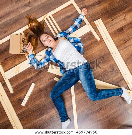 Happy woman having fun assembling furniture at home. Young girl laying on floor arranging apartment house interior. DIY. High angle view.