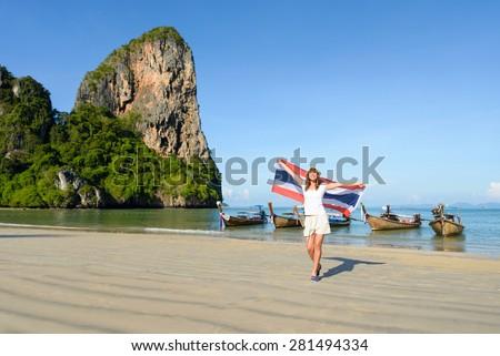 Happy woman having fun at Krabi beach with Thailand flag. Beautiful brunette enjoying travel to Asia. - stock photo