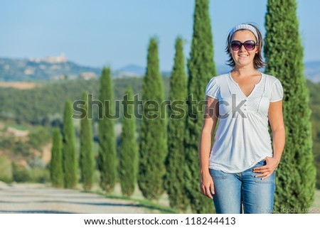 Happy woman having fun on vacations in Tuscan against cypress alley background