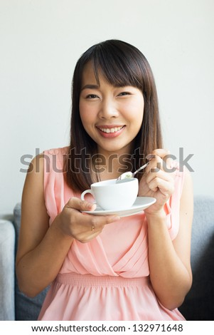 Happy woman having  morning coffee on the  sofa in bedroom