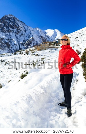Happy woman hiker walking hiking in mountains, healthy lifestyle in Himalayas in Nepal. Trekking on snow white winter nature, beautiful inspirational mountain landscape. - stock photo