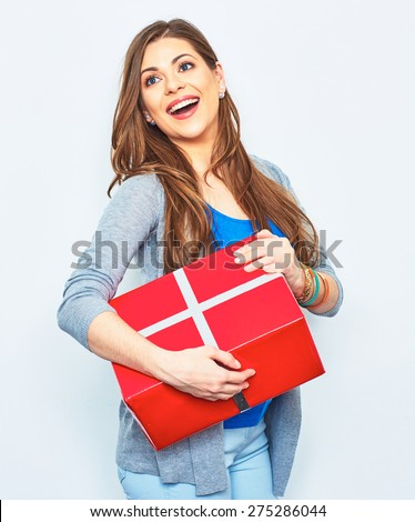 Happy Woman hold gift box. Big smile with teeth. Beautiful female model in studio. White wall background. Red gift box.  - stock photo