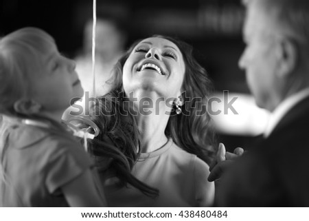 Happy woman holding a child land laughing with a head thrown back - stock photo