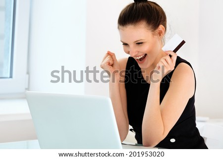 Happy Woman holding a credit card and shopping from the internet