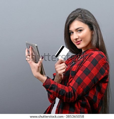 Happy woman holding a credit card and shopping from the internet against gray background - stock photo
