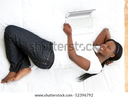 Happy woman holding a credit card surrounded with shopping bags lying on a bed - stock photo